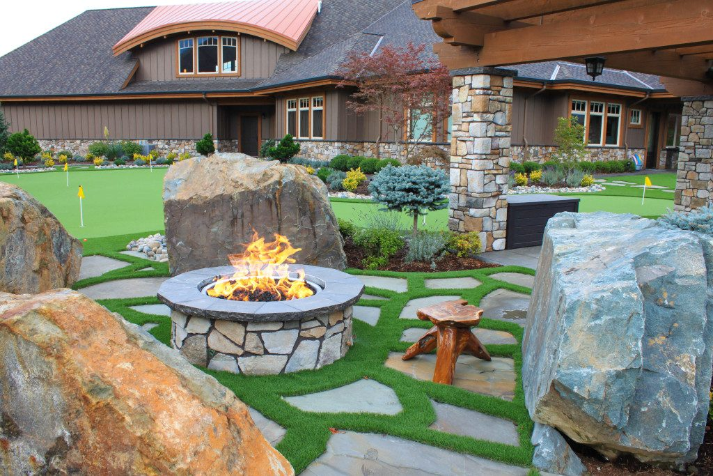 A Custom Landscape with Artificial Grass, a fire-pit and large rocks
