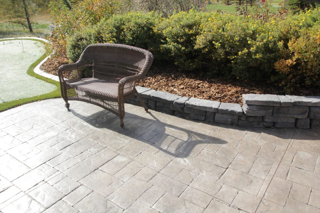 Concrete patio with park bench and artificial grass. Putting green on the left and small retaining wall.