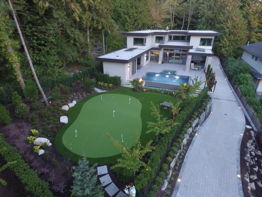 Drone shot of artificial grass putting green and pool. Landscape is backed on a green space. Stunning large concrete driveway.