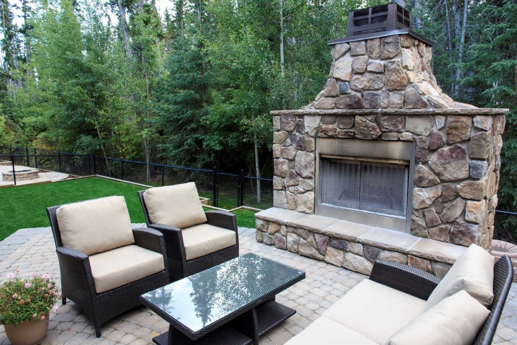 Fireplace with Riverstone and concrete patio surrounded with green lawn. Backed on large green space.