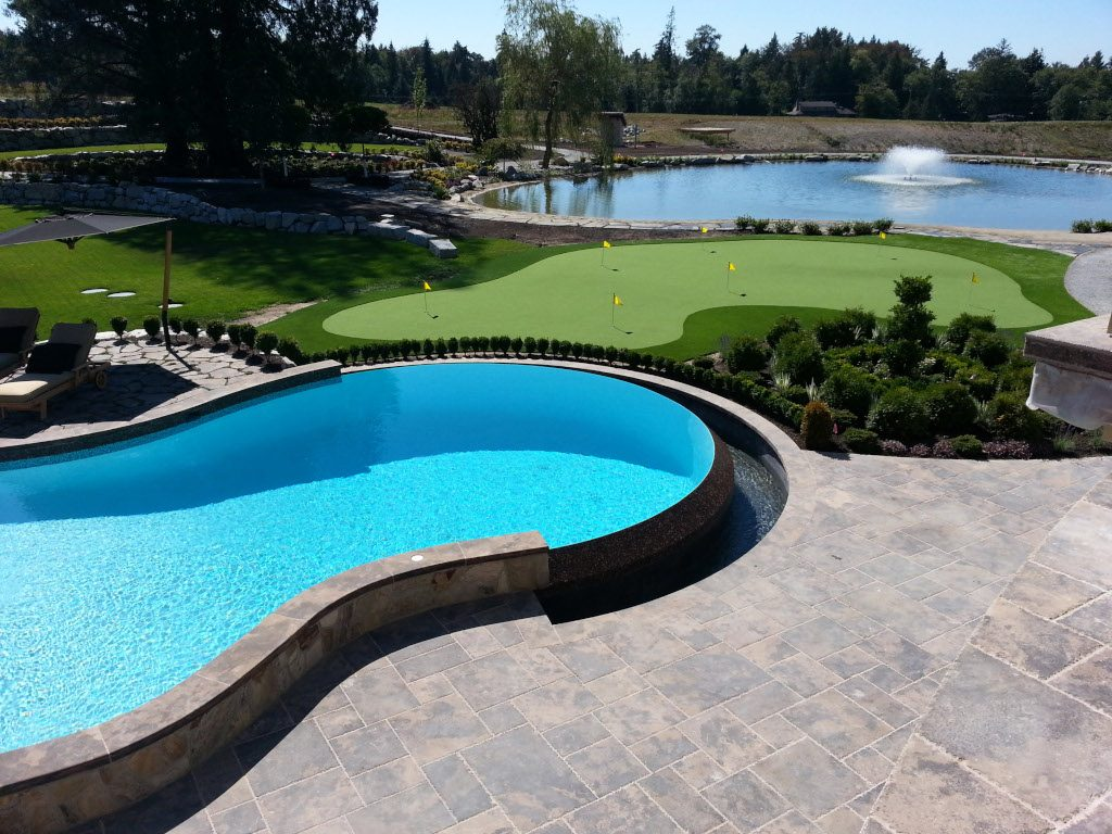 Large circular swimming pool on a golf course and artificial grass. Backed on a large storm pond with fountain.