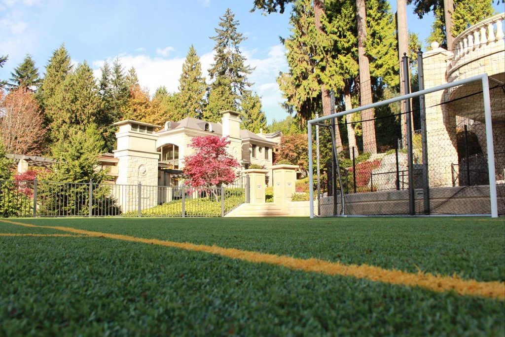 Side view of Astro turf or synthetic lawn. A football or soccer field with goal posts.